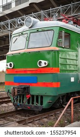 Green locomotive with red stripes on the cabin stands on the railway station