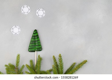 green lollipops shaped christmas tree with christmas tree branches and white snowflakes on blue background. Invitation, christmas celebration. xmas and new year card top view flat lay copy space