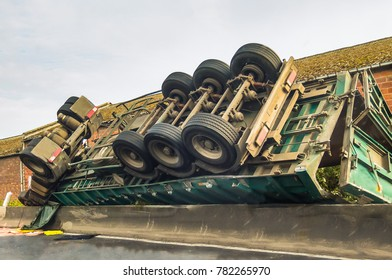 green lorry, truck crashed at the sde of a road it has fallen over the side of the crash barrier and is upside down with wheels in the air