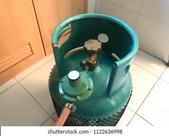 Green LPG cooking gas tank or propane cylinder with safety valve and regulator in household, angle view