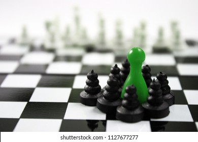Green ludo king and chess black pawns group around him and stares out into the white blurry army