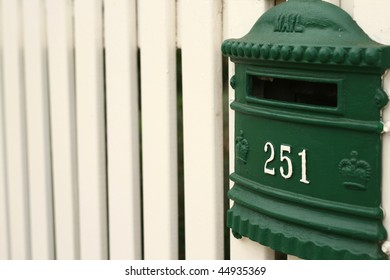 green mailbox on cream white picket fence