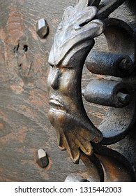 Green Man cast iron decorative door handle of face surrounded by leaves. Detailed closeup of naturalistic pagan symbol on traditional antique wooden door background in south France
