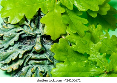 Green man pagan icon and oak leaves, close up image.
