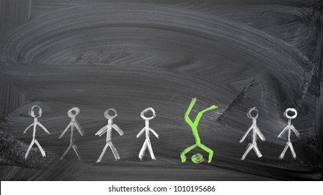 Green man painted chalk on a blackboard standing on the head out from crowd of plenty identical white fellows. Leadership, uniqueness, independence, initiative, strategy, dissent, business concept.