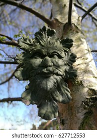 Green man sculpture hanging in a tree