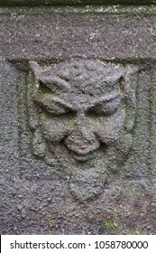 Green Man in stone on ancient pedestal