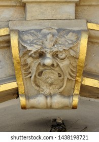 Green man stone relief in white and gold on the facade of an old building gate in Old Town Market Place, Warsaw, Poland