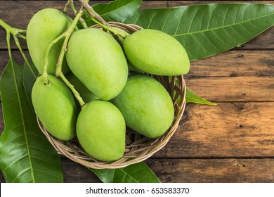 green mango and green leaf on basket and old wooden floor background,Group of raw mangoes organic with sour and high vitamin C fruit for healthy.