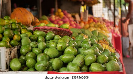 Green mangoes with other fruits in a fruit stand in a market. Vendor at the background.