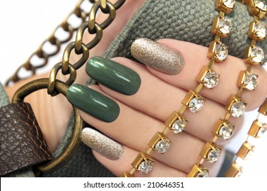 Green manicure with a brilliant gold lacquer on oval shaped nails.