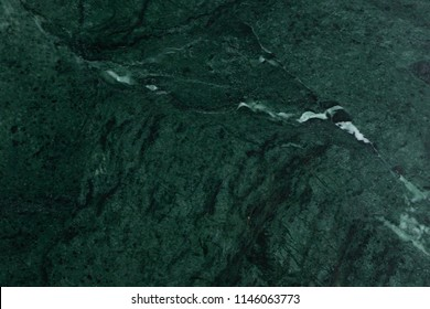 Green marble surface close up texture. Malachite deep green natural color texture. Detailed close up background of malachite gemstone in high resolution