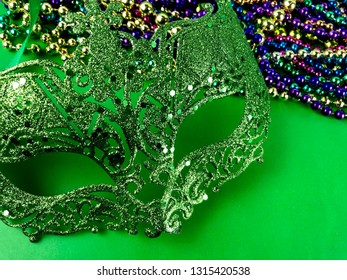 Green Mardi Gras mask and beads on a green background