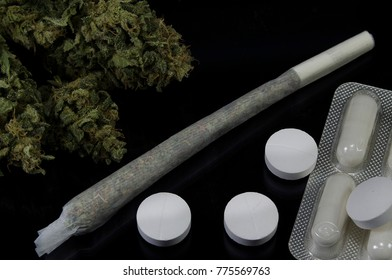Green marijuana buds with joint laying with pharmacy pills on black background