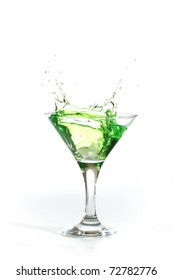 green martini cocktail splashing into glass on white background
