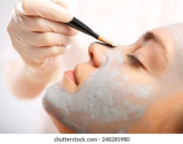 Green mask, woman in spa salon.Cosmetic moisturizing mask is applied to the face of a woman. Cleansing mask, mask with green clay, relax in the spa