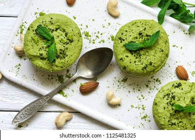 green matcha and banana vegan raw cakes with mint and nuts over white wooden table with a spoon. healthy delicious food. top view