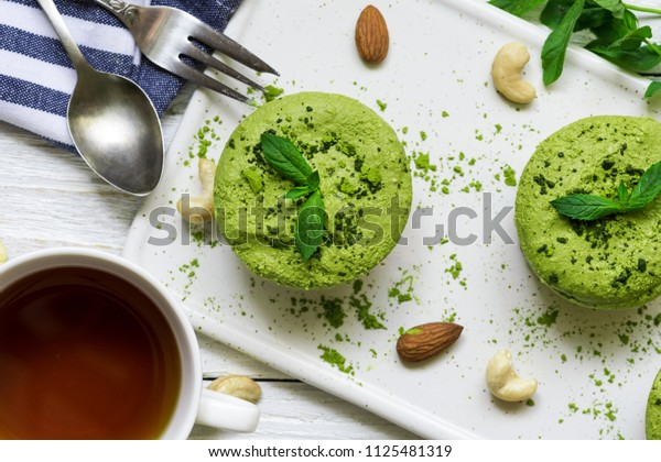 green matcha and banana vegan raw cheesecakes with mint and nuts over white wooden table with cup of tea and spoon. healthy delicious breakfast. top view