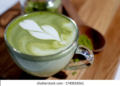Green matcha latte with latte art in transparent mug on wooden desk table at loft style lines coffee shop, commercial advertisement background. Healthy superfood with plant based vegan milk.