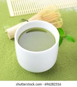 Green matcha tea in a bowl and bamboo whiskon