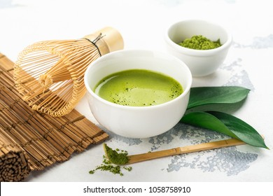 Green matcha tea drink and tea accessories on white background. Japanese tea ceremony concept. Copy space