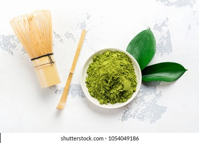 Green matcha tea powder and tea accessories on white background. Japanese tea ceremony concept. Copy space