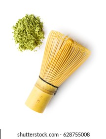 Green matcha tea powder and bamboo whisk isolated on white background.