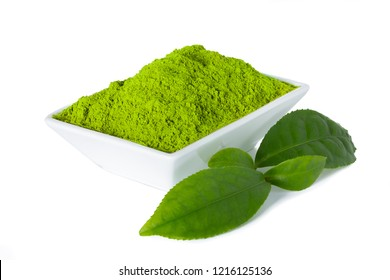 Green matcha tea powder in white bowl with green tealeaves isolated on white background