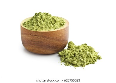 Green matcha tea powder in wooden bowl isolated on white background.
