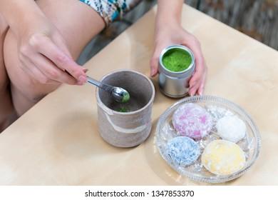 Green matcha teacup and mochi rice cake Japanese dessert wagashi colorful daifuku with woman girl hand preparing tea powder measuring spoon on table