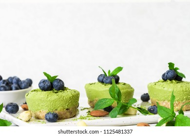 green matcha vegan raw cakes with blueberries, mint and nuts. healthy delicious food. close up