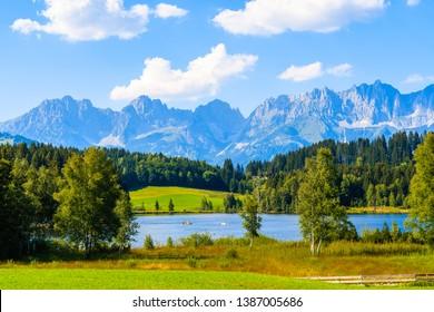 Green meadow against Alps mountains near Schwarzsee lake on sunny beautiful summer day near Kitzbuhel, Tyrol, Austria