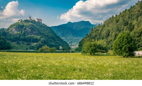 Green meadow with at the background an Italian style castle on the top of a hill