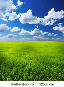 Green meadow blue sky and white clouds