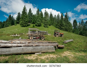 Green meadow and forest with tractor and logs in Transylvania