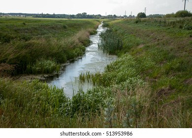 green meadow with irrigation ditch in village