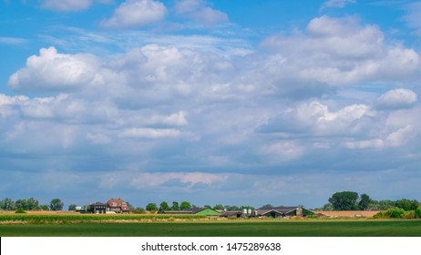 Green meadow landscape in front of a modern farm and an typical old Dutch house with a dike in the background, Dutch Polder Landscape