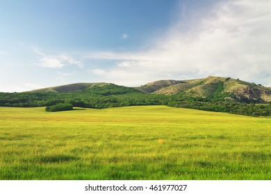 Green meadow in mountain and blue sky. Composition of nature.