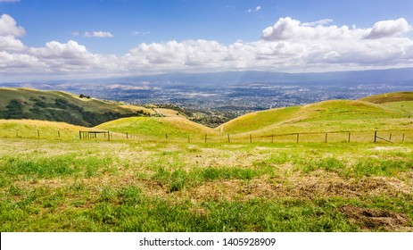 Green meadow on the hills of South San Francisco bay area; San Jose visible in the background; California