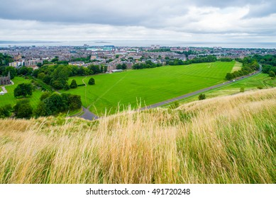 Green meadow, Queen's Dr and north area of Edinburgh city below Holyrood Park hill in Autumn.