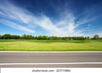 green meadow with trees and asphalt road, blue sky on background