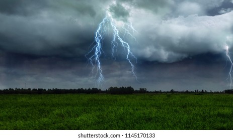 Green meadow under Thunderstorms and lightning, Outdoor countryside meadow grass nature. Rural grass field landscape. Background photography of natural rainy season landscape.