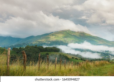 Green meadows, clouds flying low above the ground, clouds and small village houses in the French pyrenees on a bright summer sunny day. Mountain life, calm and solitude. Camino de Santiago landscapes.