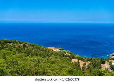 green mediterranean hill next to the blue sea