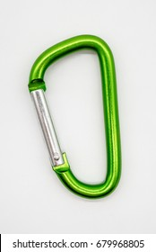 Green metal aluminum snap hook isolated on white background. Safety lock carabiner for rope climbing