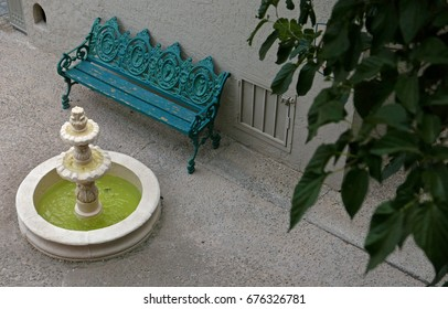 Green metal bench in front of a small fountain, seen from above