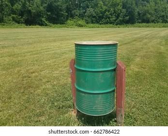 green metal garbage can in field