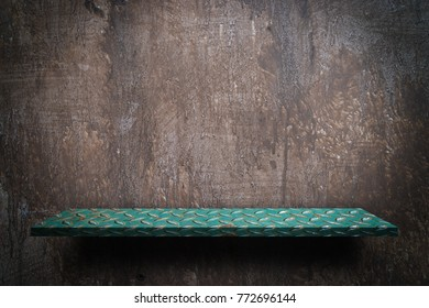 Green metal shelf display counter on grungy wall
