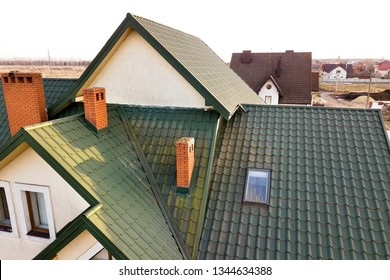 Green metal shingled house roof with attic plastic window and brick chimney.