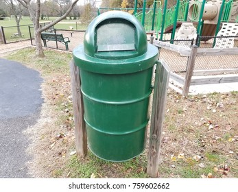 green metal trash can with play structure in background
